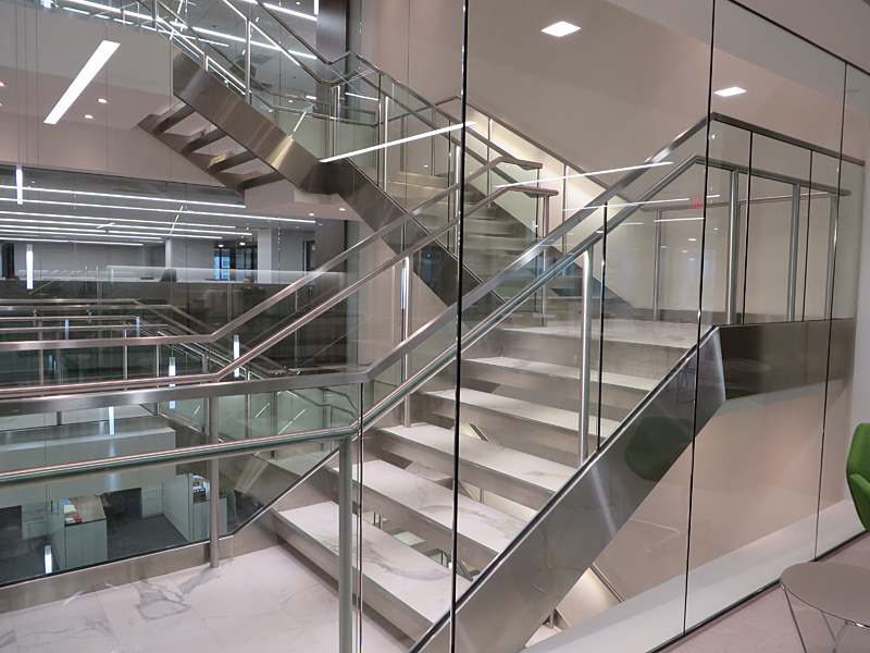 Decorative metal stair featuring illuminated stainless steel handrail.