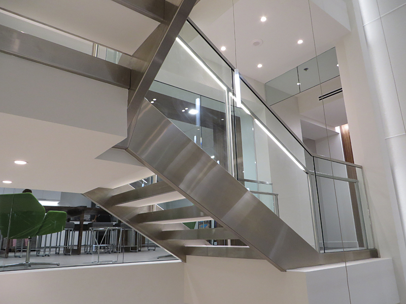 Stainless steel decorative metal stair featuring illuminated stainless steel railing.