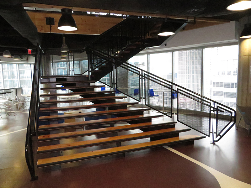 Cantilevered decorative metal stair with wood treads