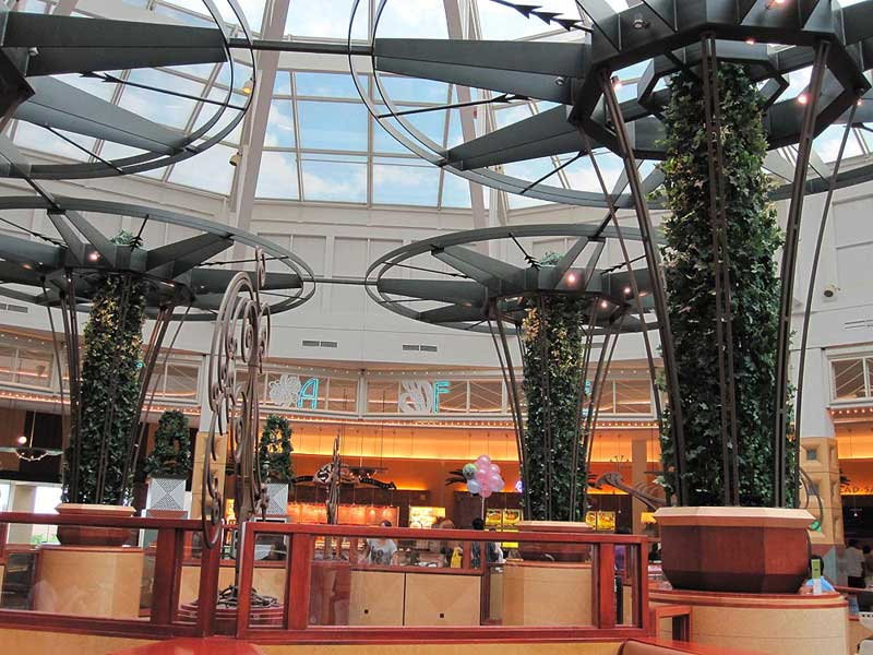 Large decorative iron trellises with round tops and plants growing up through the center