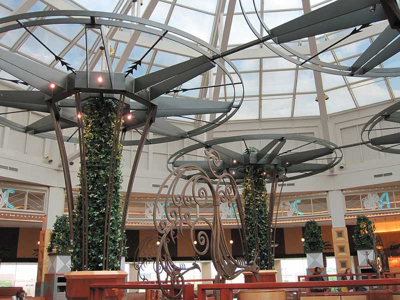 Large decorative iron trellises with round tops and plants growing up through the center at Somerset mall