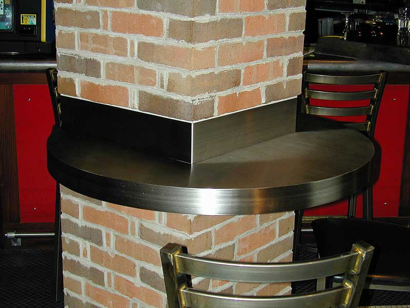 Custom stainless steel bar table counter attached to brick column.