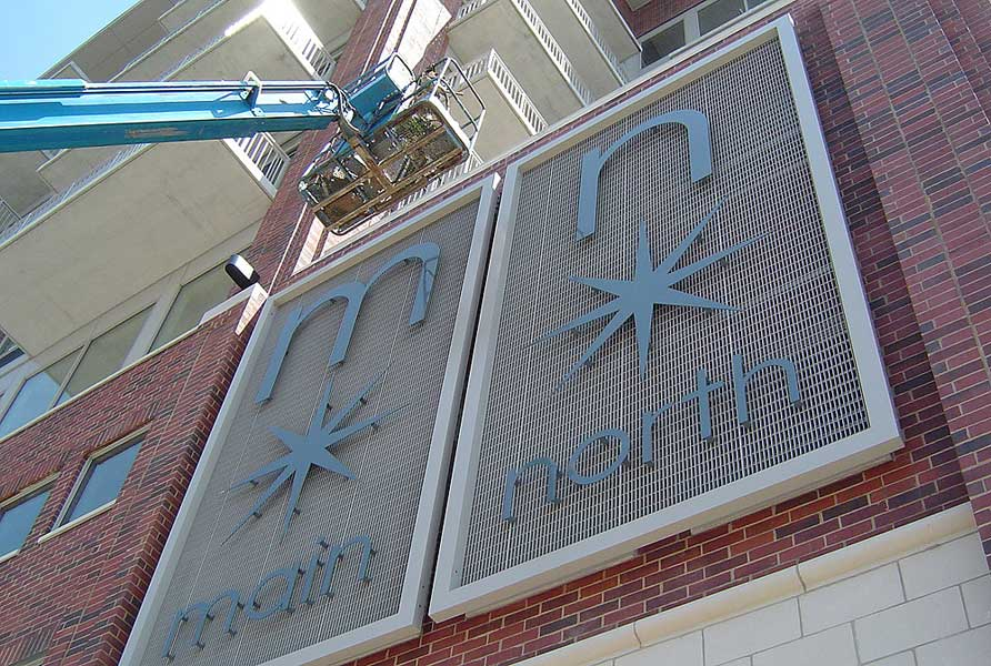 Custom fabricated water jet cut exterior sign is hoisted by crane into place at Main North Loft's