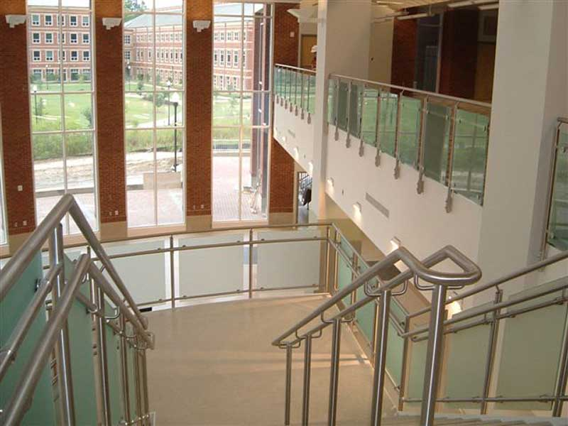 Staircase with fabricated stainless steel railings with frosted glass