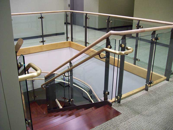 Ornamental custom metal railings at balcony fabricated using tempered glass panels, brass sub-rails and wood cap rail.