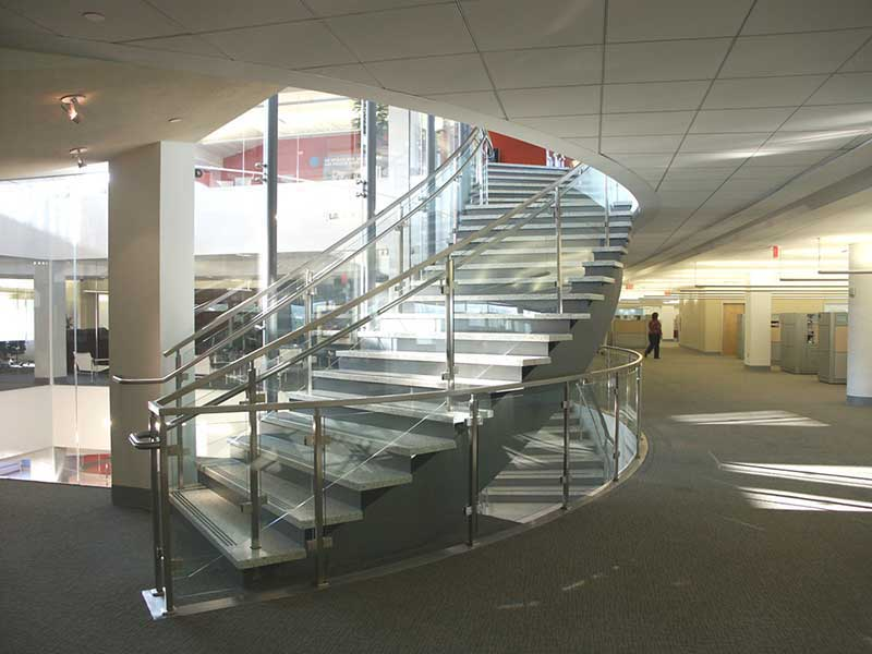 Curved multi flight decorative staircase with glass and stainless steel railings.