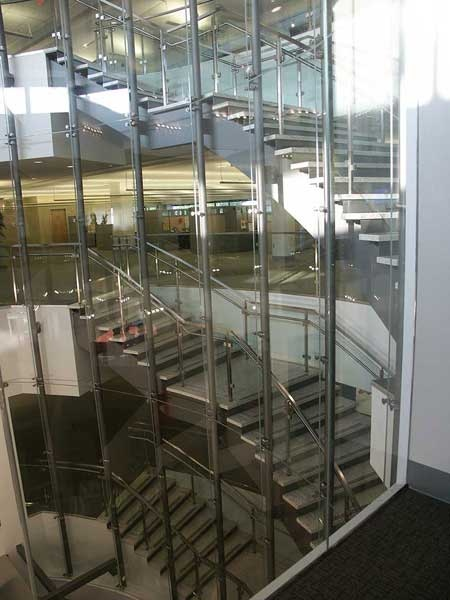 Curved stairway separated by glass wall.