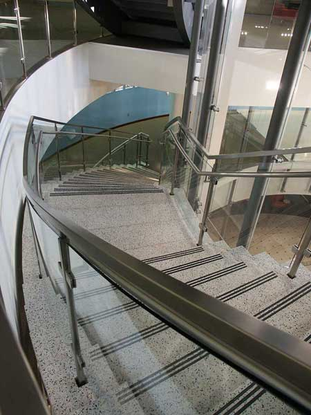 Tempered curved glass railings with custom stainless steel post, glass clamps and handrail.