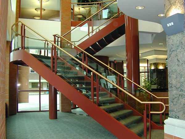 Steel plate stringer with glass and brass handrail. All connections on brass handrails are fully welded and polished.