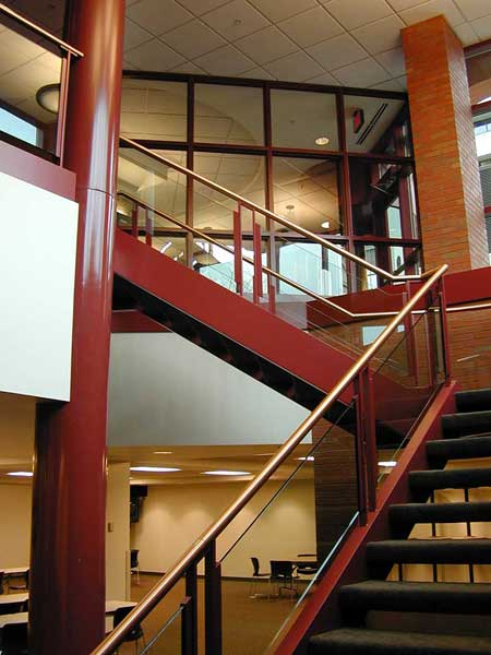 Switchback metal stair with glass and brass handrail.
