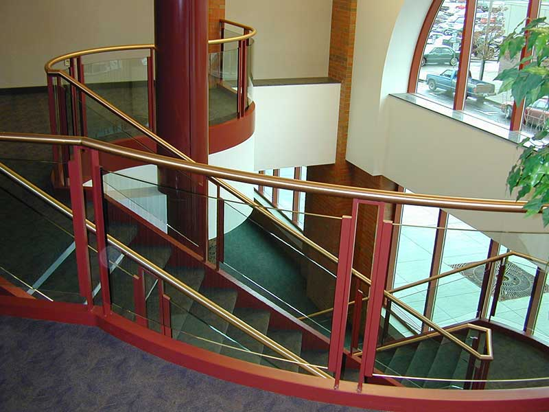 View of curved brass and glass railings at balcony.