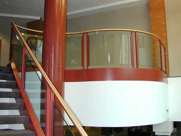 Glass railings at balcony with brass pipe top handrail.