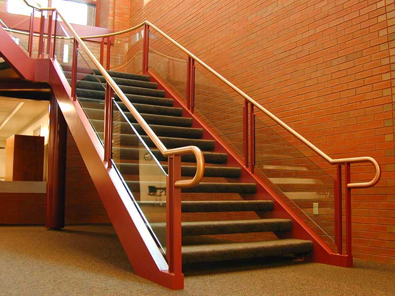 Decorative stair with custom brass and glass rails.