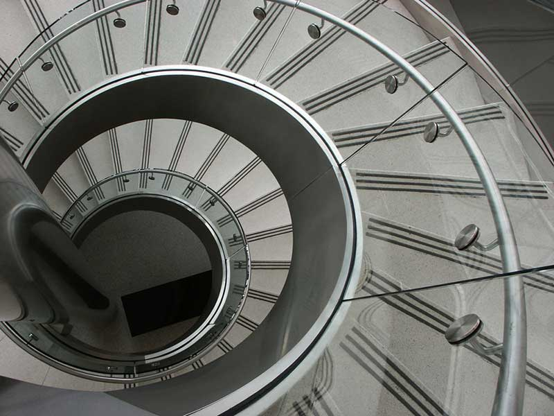 View of curved circular stair from top looking directly down the center of stairs.