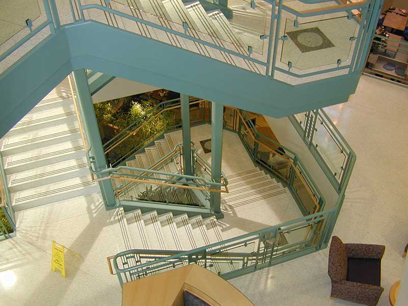 Beautiful ornamental stair with glass and wood handrail.
