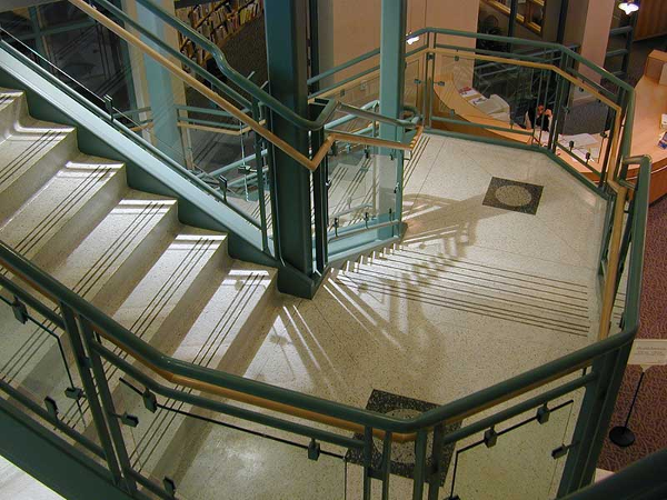 Green painted stairway with ornamental glass rails.