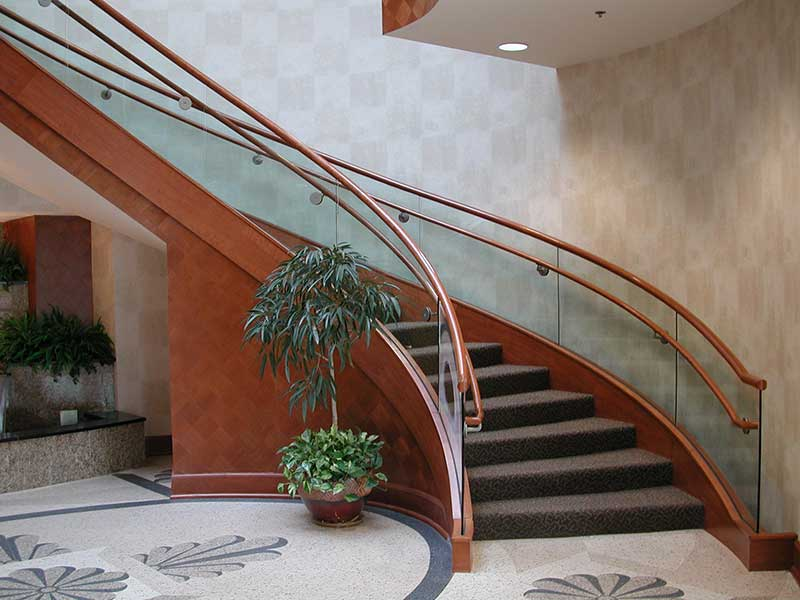 Wood curved stairway with carpet treads