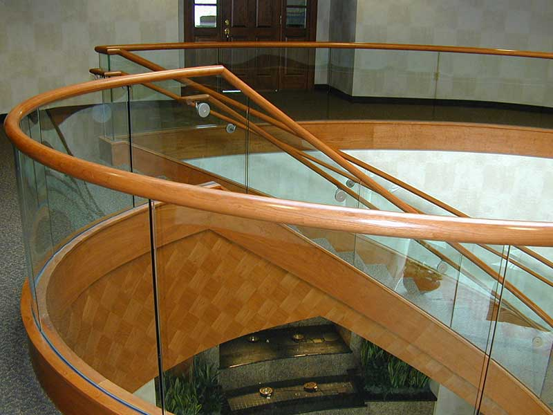 Custom wood railing on top of curved glass railings